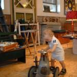 In der Antikscheune gibt es viel zu entdecken. Kind mit antikem Fahrzeug.